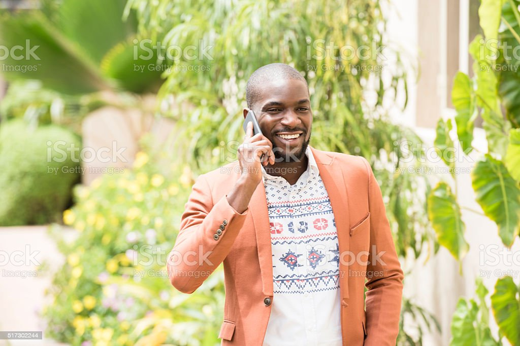 Nigerian man in orange jacket on cell phone, smiling stock photo