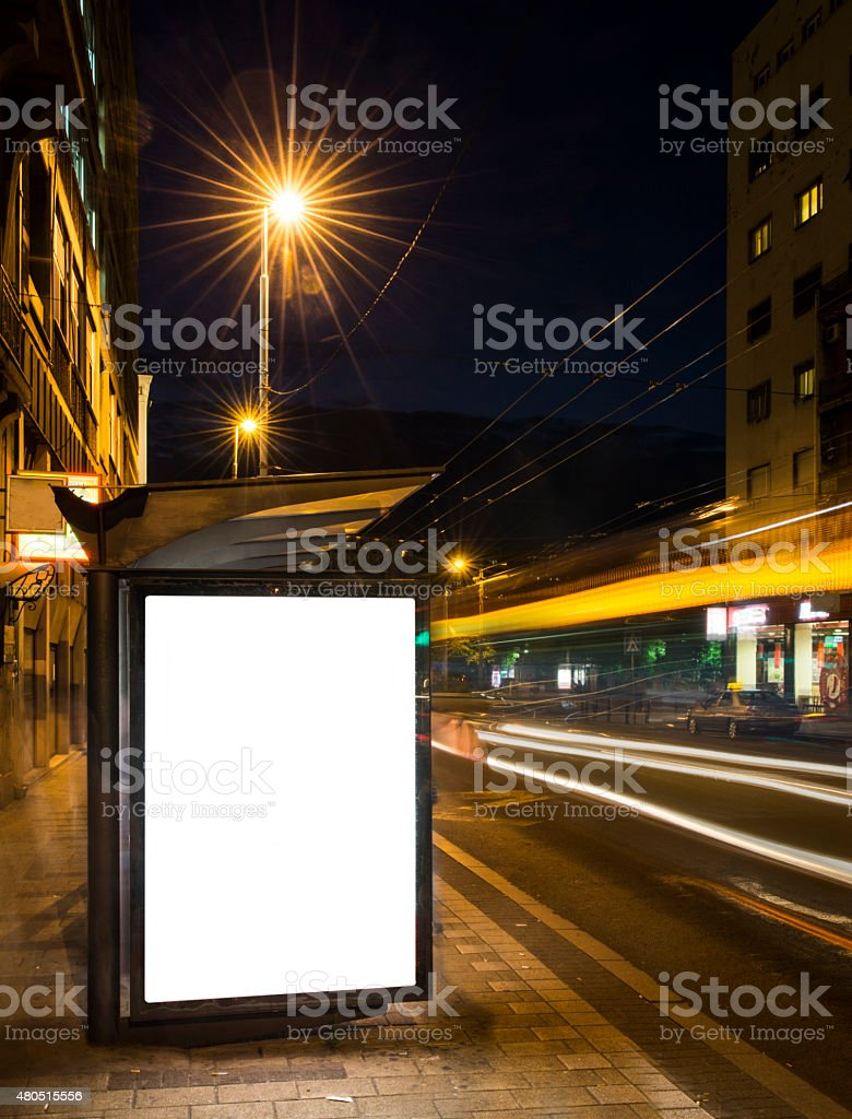 Night bus station with blank billboard stock photo