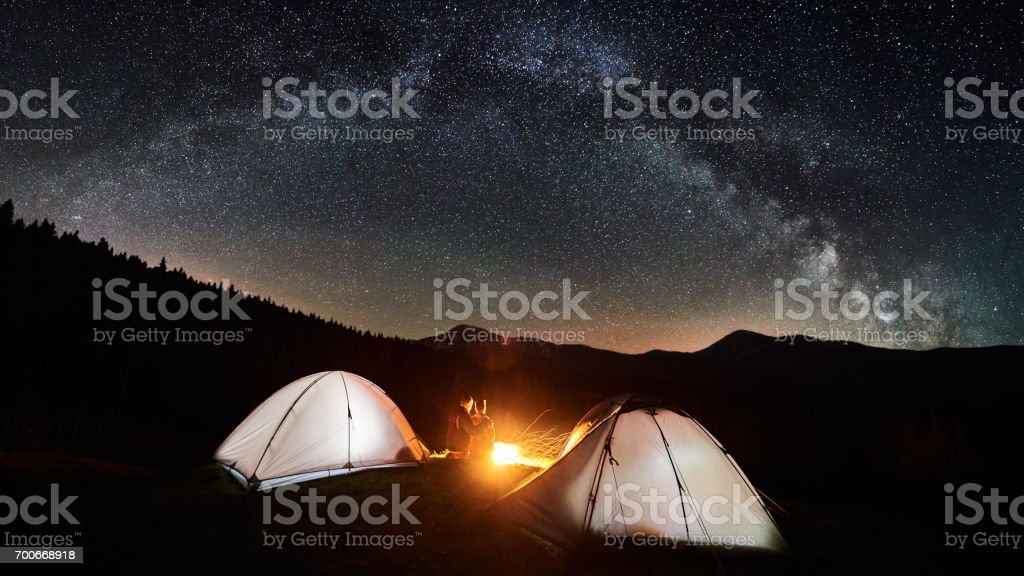 Night camping. Couple tourists sitting and hugging at a campfire near two illuminated tents under beautiful night sky full of stars and milky way. Long exposure. Picture aspect ratio 16:9 stock photo