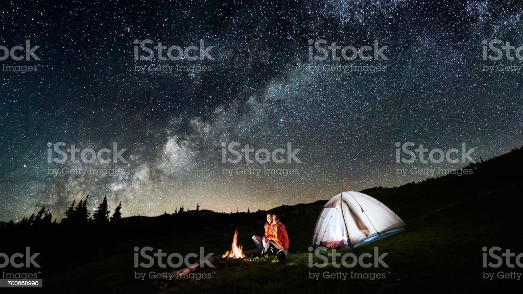 Night camping. Couple tourists sitting at a campfire near illuminated tent under incredible night sky full of stars and milky way. Long exposure. Picture aspect ratio 16:9 stock photo