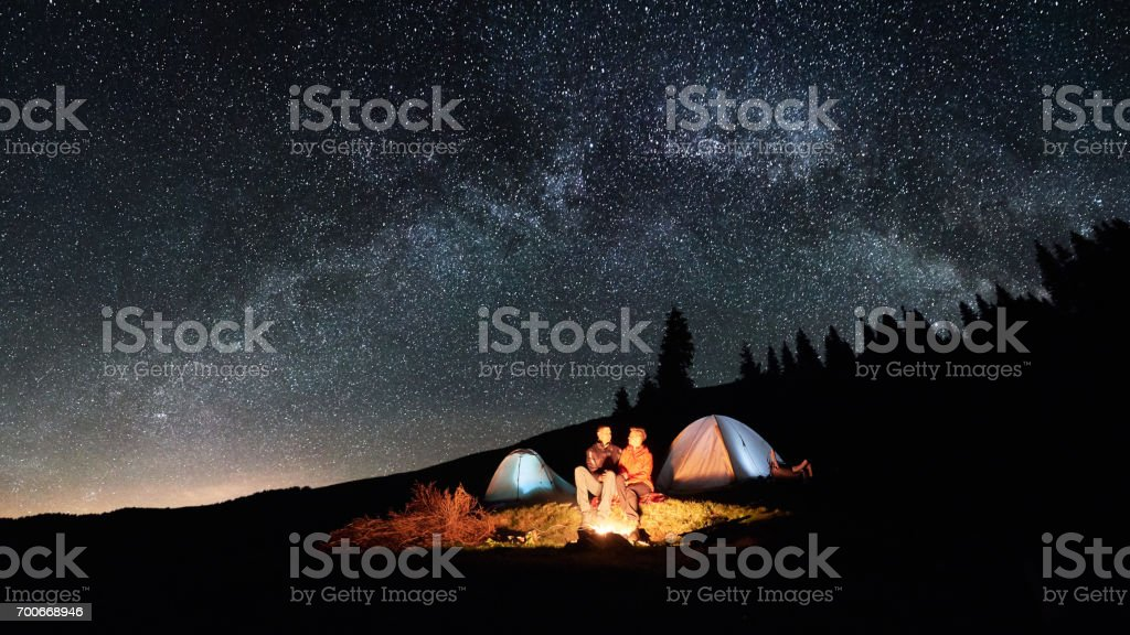 Night camping. Couple tourists sitting at a campfire near two illuminated tents under beautiful night sky full of stars and milky way. Long exposure. Picture aspect ratio 16:9 stock photo