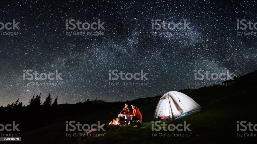 Night camping in the mountains. Couple tourists have a rest at a campfire near illuminated tent under amazing night sky full of stars and milky way. Low light. Picture aspect ratio 16:9 stock photo
