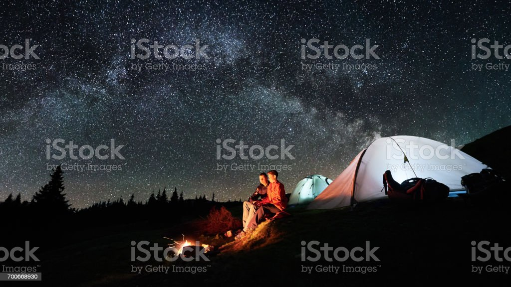 Night camping in the mountains. Man and woman tourists sitting at a campfire near two illuminated tents under beautiful night sky full of stars and milky way. Long exposure. Picture aspect ratio 16:9 stock photo