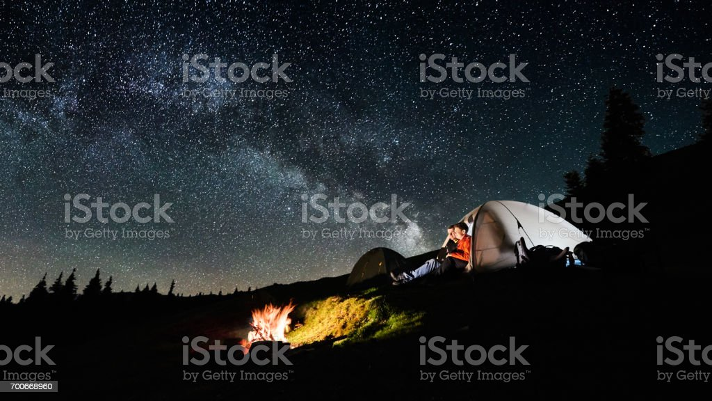 Night camping. Man and woman tourists sitting in the illuminated tent near campfire under amazing night sky full of stars and milky way. Long exposure. Picture aspect ratio 16:9 stock photo