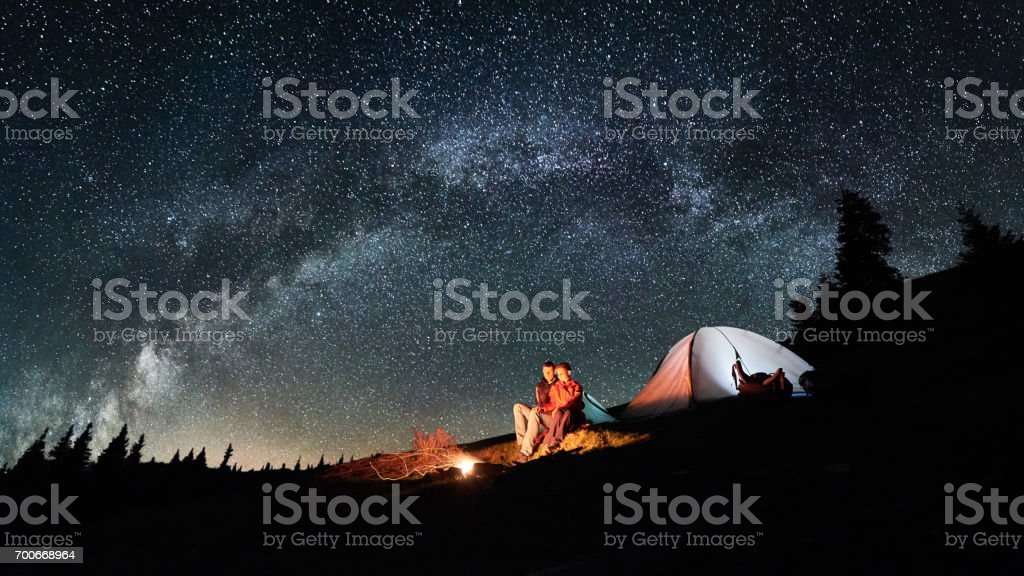 Night camping. Romantic couple tourists have a rest at a campfire near illuminated tent under amazing night sky full of stars and milky way. Astrophotography. Picture aspect ratio 16:9 stock photo