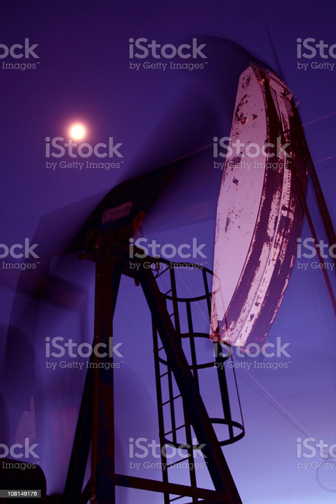 night drilling for oil under a full moon royalty-free stock photo