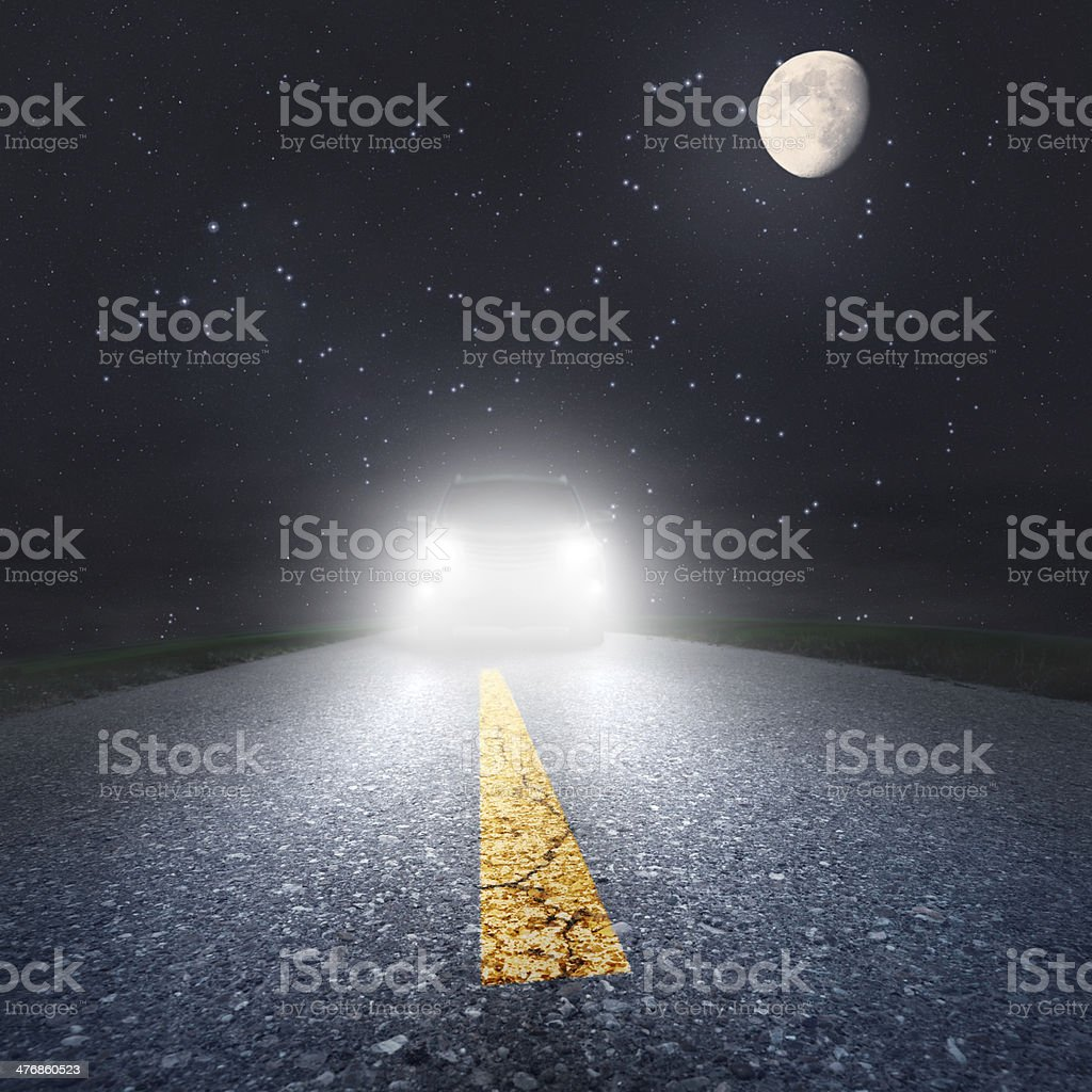 Night driving on an asphalt road towards the headlights stock photo