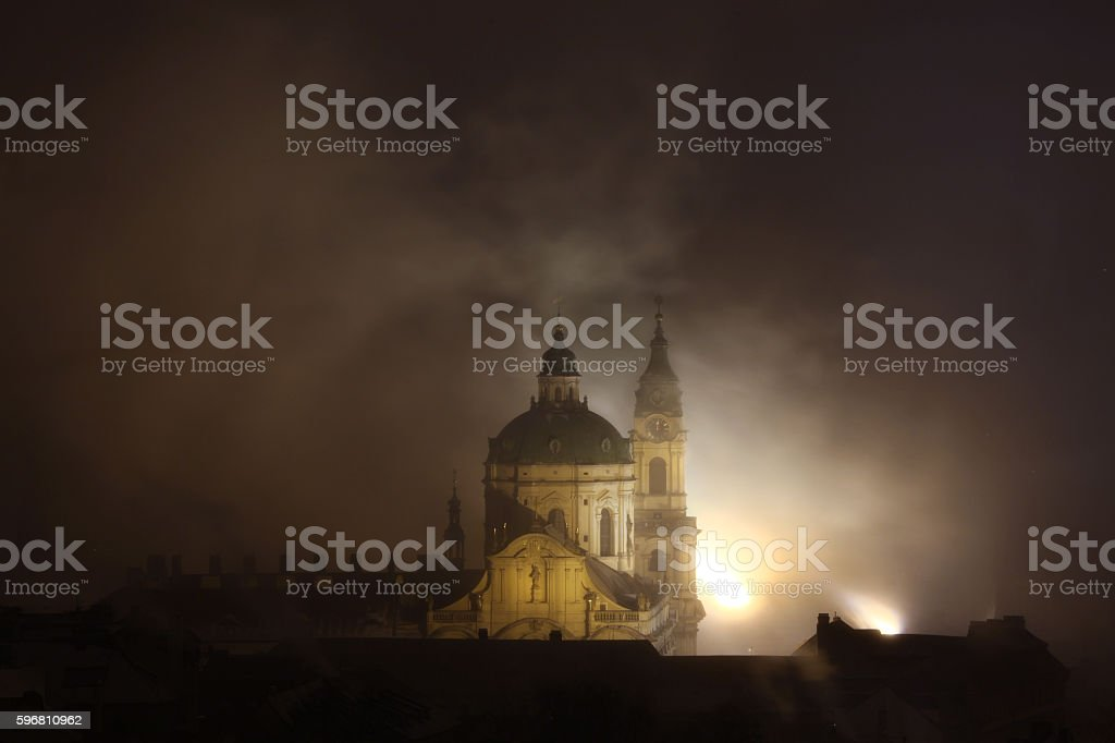 Night fog over Saint Nicholas Church in Prague, Czech Republic. stock photo