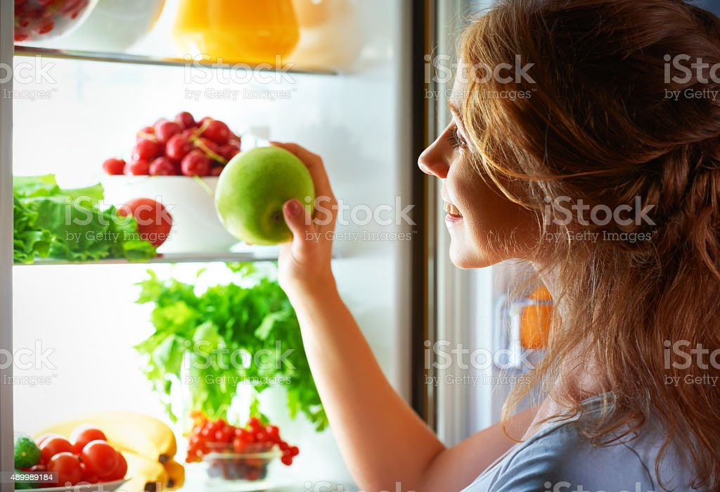 night hunger. Woman in the dark at open refrigerator stock photo
