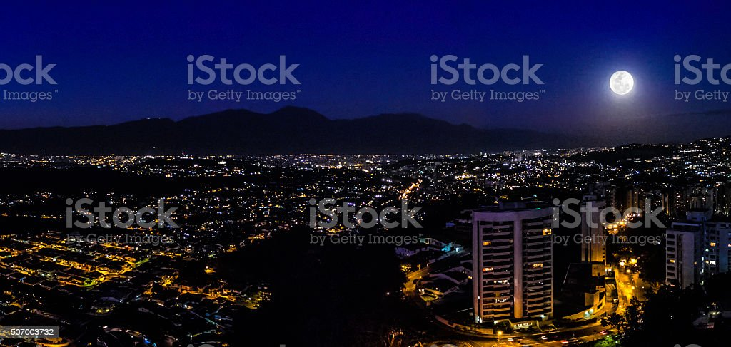 Night image of Caracas city aerial view with full moon stock photo