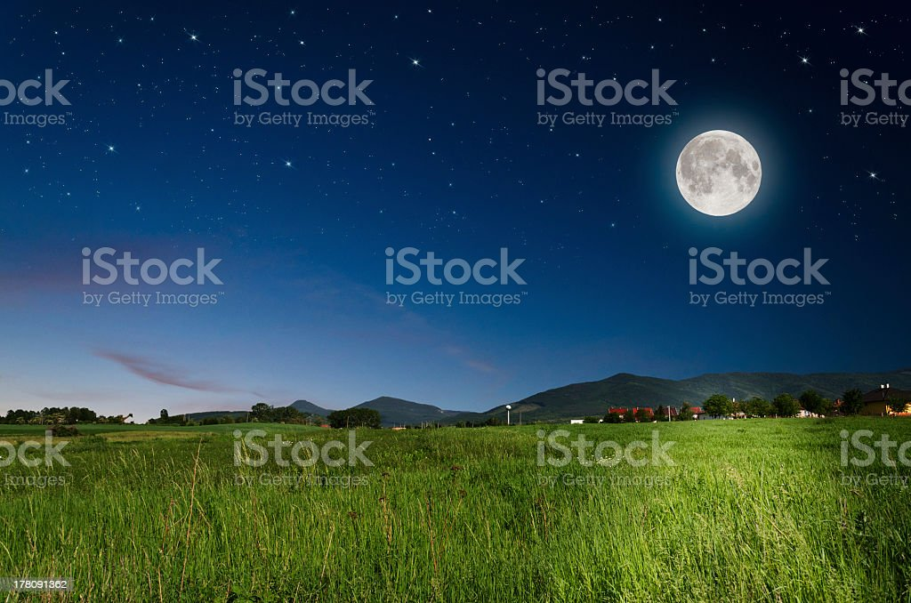 Night landscape with bright full moon over field stock photo