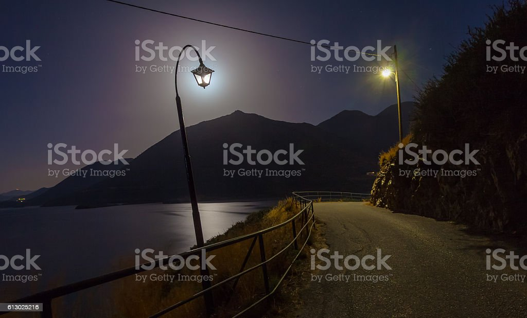 Night landscape with lamps near the road, mountains, sea, moon stock photo