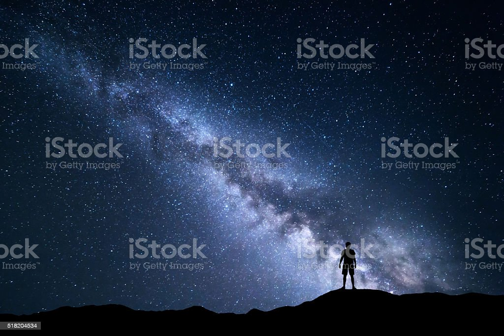 Night landscape with Milky Way and silhouette of a man stock photo