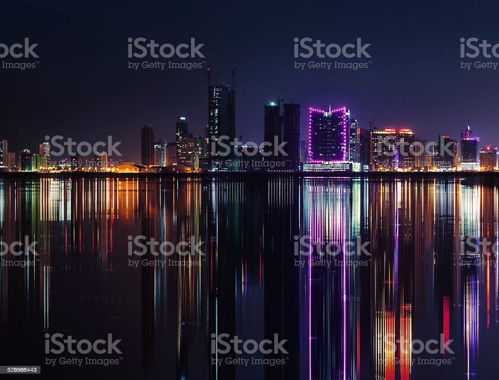 Night modern city skyline with neon lights and reflections stock photo