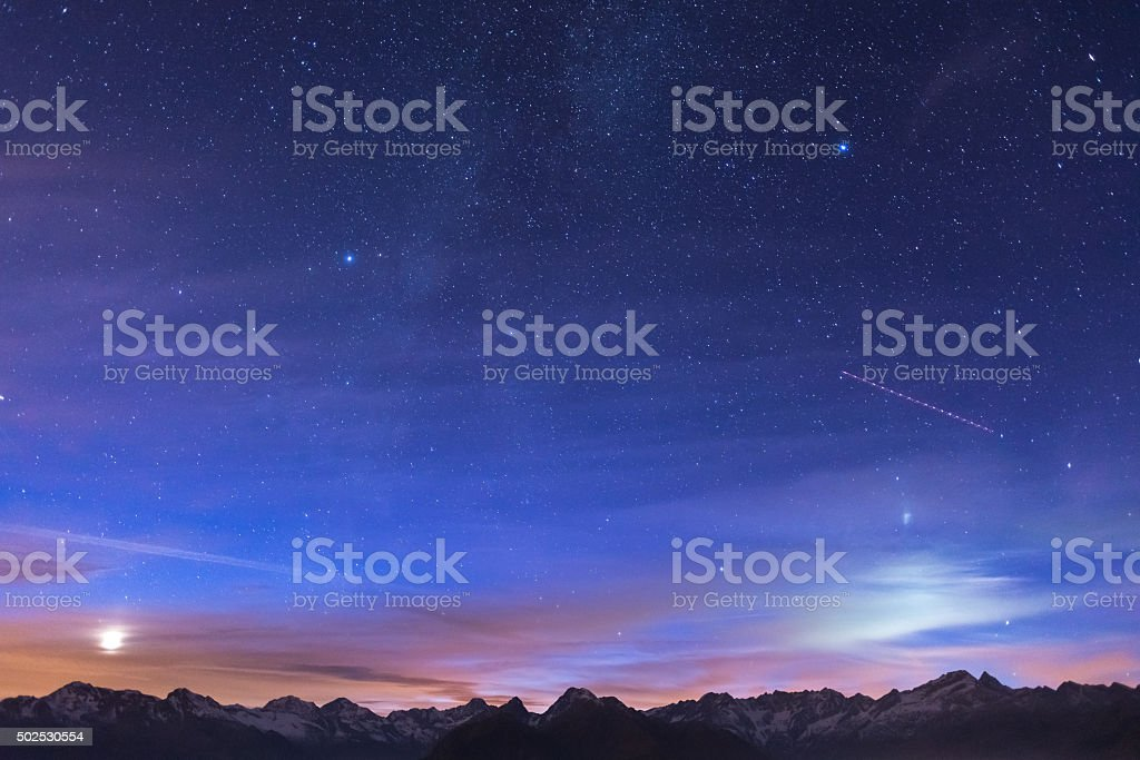 Night on the Alps under starry sky and moonlight stock photo