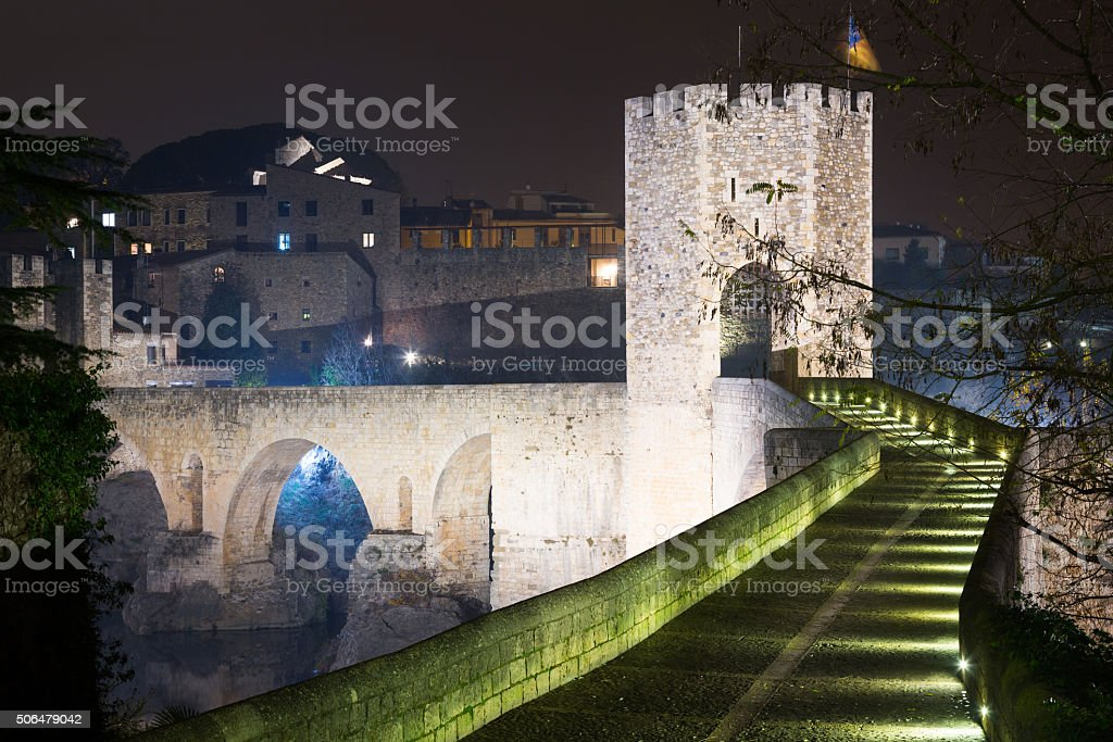 night photo of old medieval stone bridge with gate stock photo