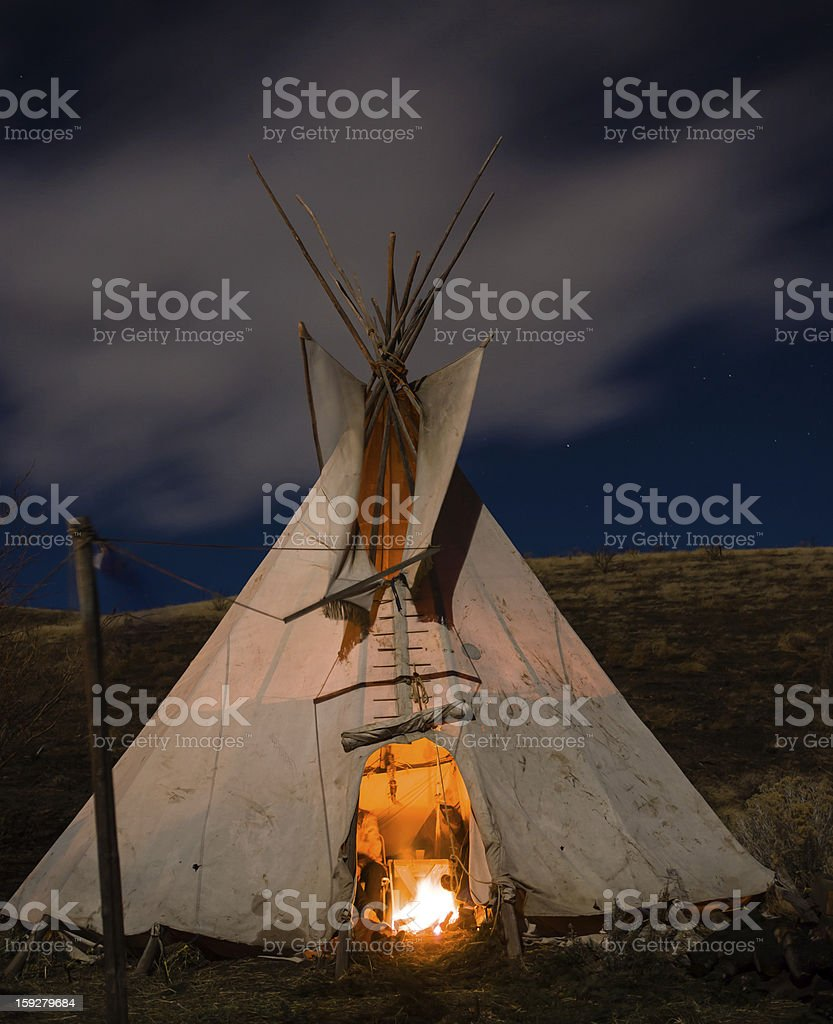 Night photograph of a Native American teepee with a fire stock photo