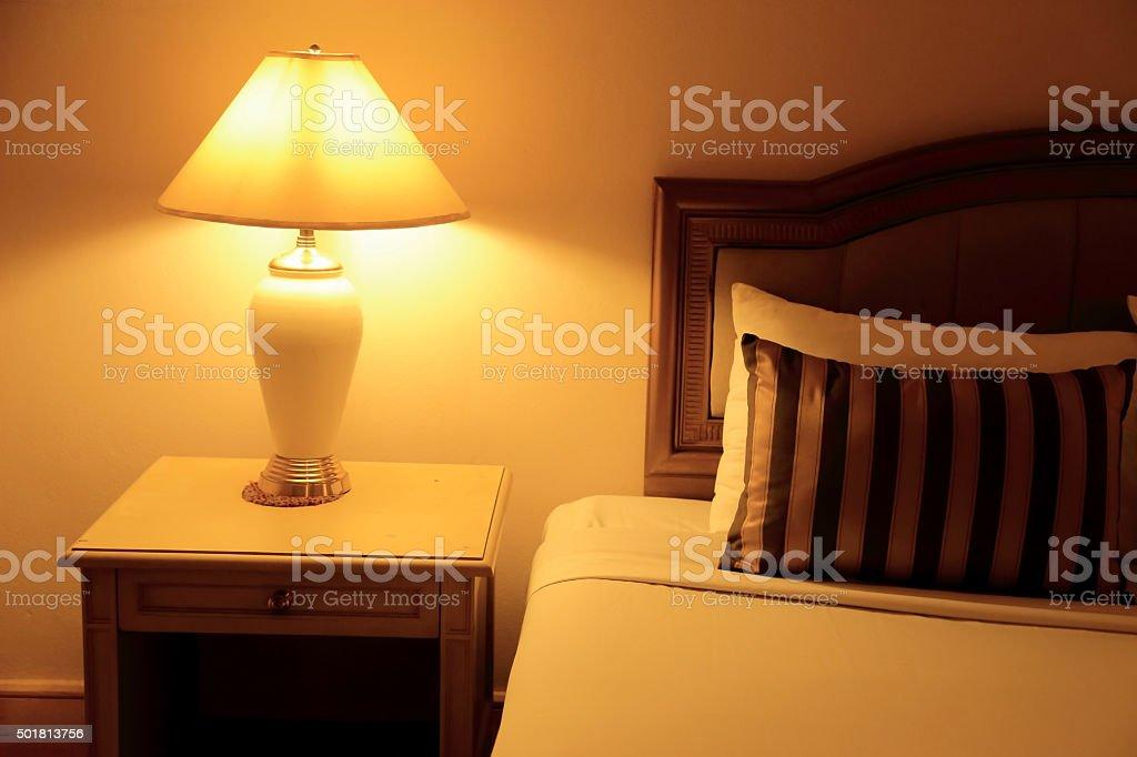 Night scene image of hotel room interior, comfortable bed. stock photo