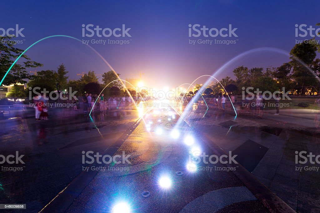 night scene of street with fountain and people in hangzhou stock photo