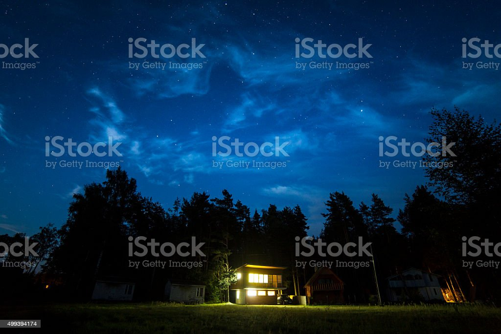 Night scene with small cottage and stars in the sky stock photo