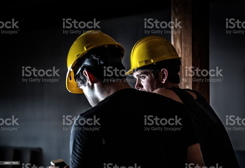 Night Shift Construction Worker Texting During Rest Break stock photo