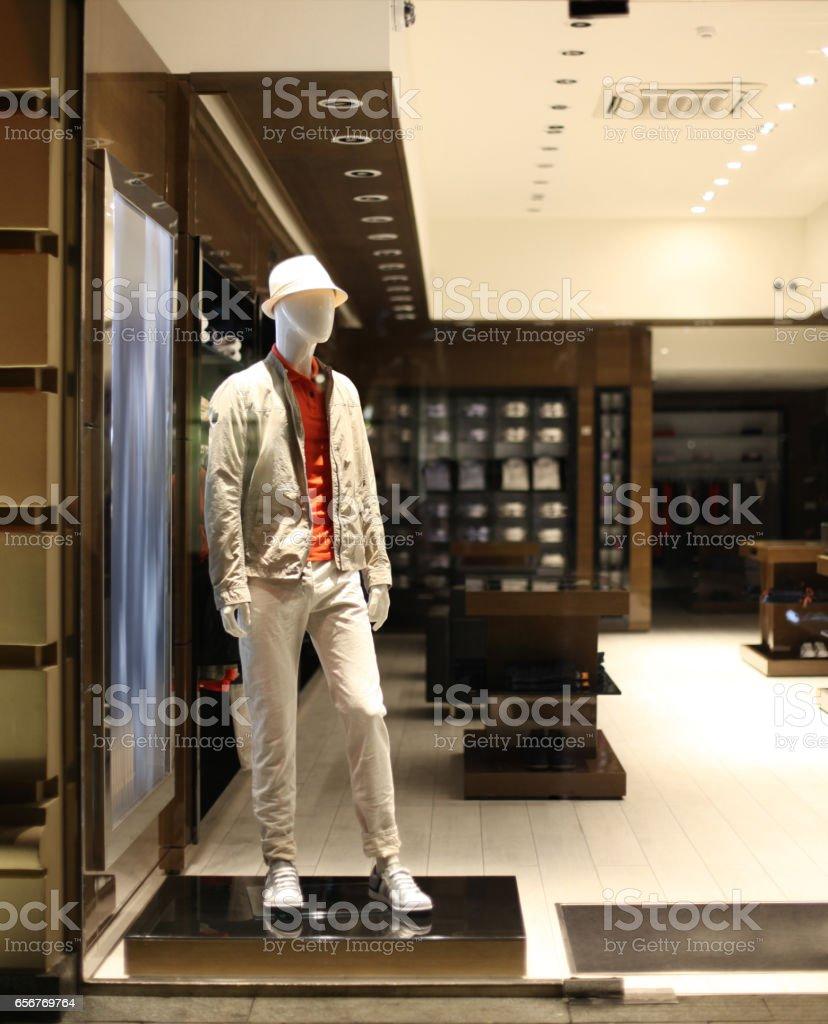 Night shop window with men dressed mannequins. Evening warm lihgt. stock photo
