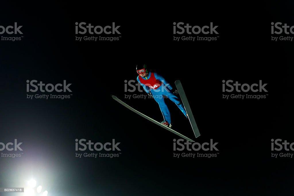 Night Shot of Ski Jumper in Mid-air stock photo