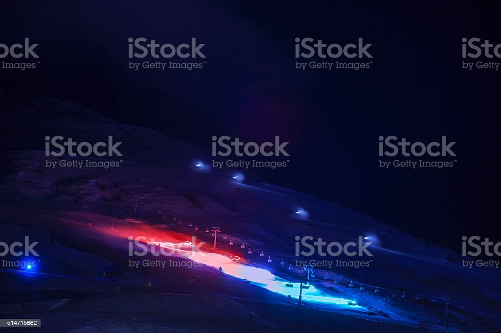 Night skiing  Large ski group of skiers with color lights stock photo
