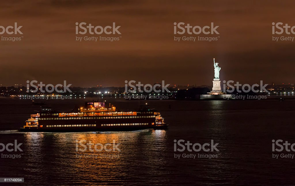 Night sky with Ferry and Statue of Liberty stock photo