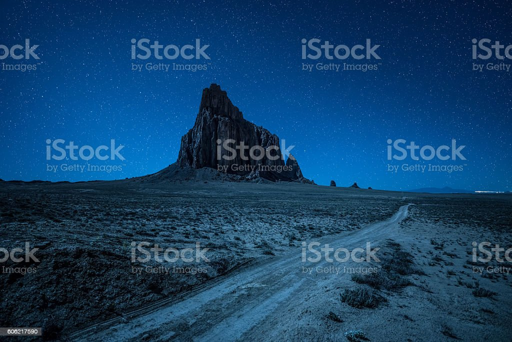 Night sky with many stars above Shiprock in New Mexico stock photo