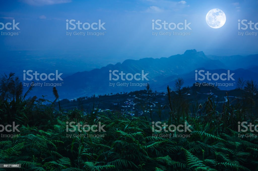 Night sky with sunbeam, foggy is swingin above mountain peak. stock photo