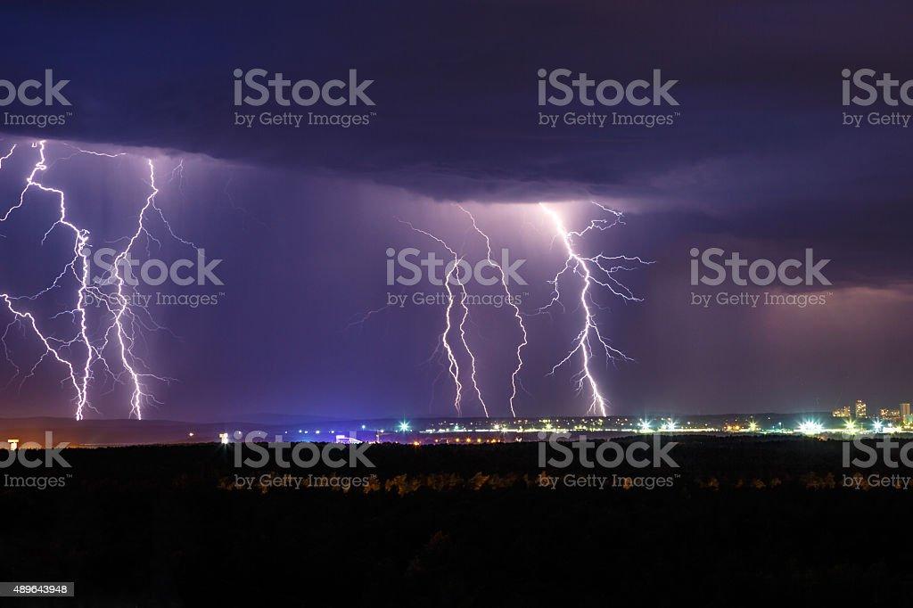 Night thunder lightning over the city sky stock photo