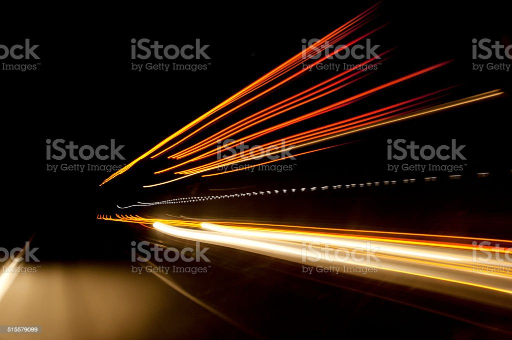 Night time highway blurred stream of light as trucks pass stock photo