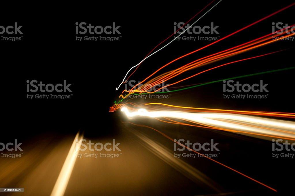 Night time highway blurred stream of light as trucks pass stock photo