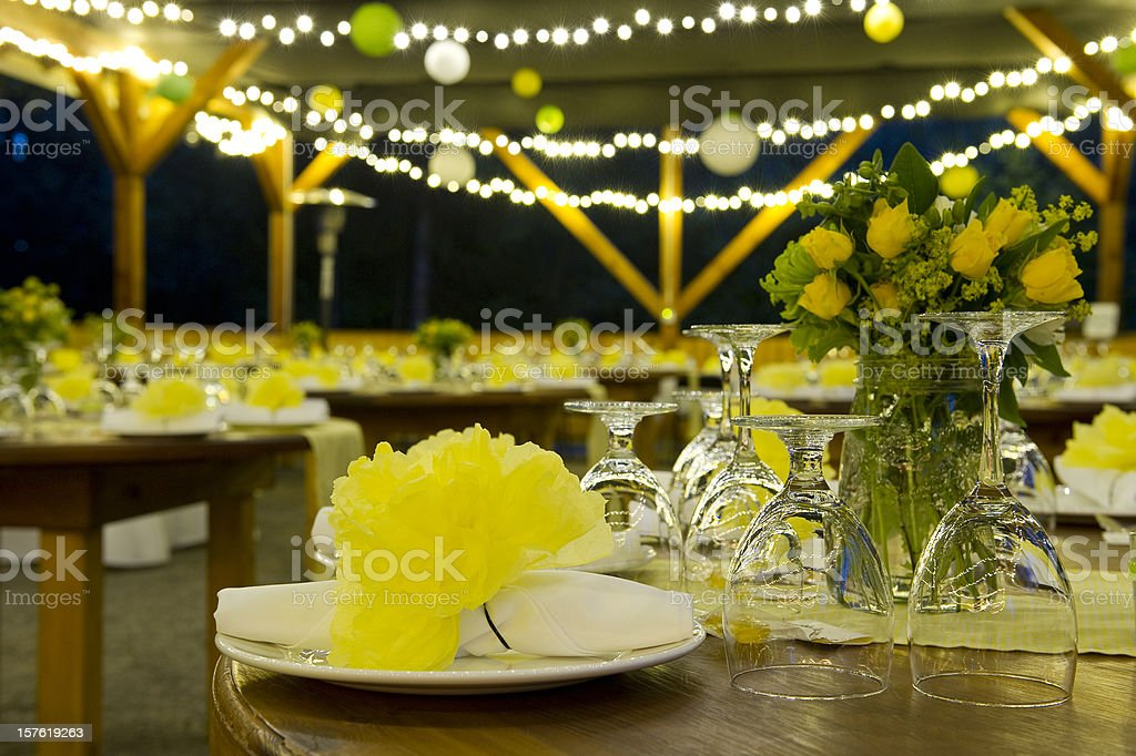 Night time wedding with yellow flowers and strings of light royalty-free stock photo