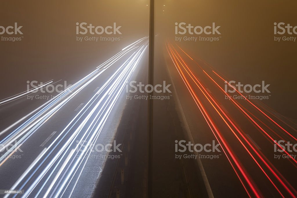 Night traffic on a highway in the fog stock photo