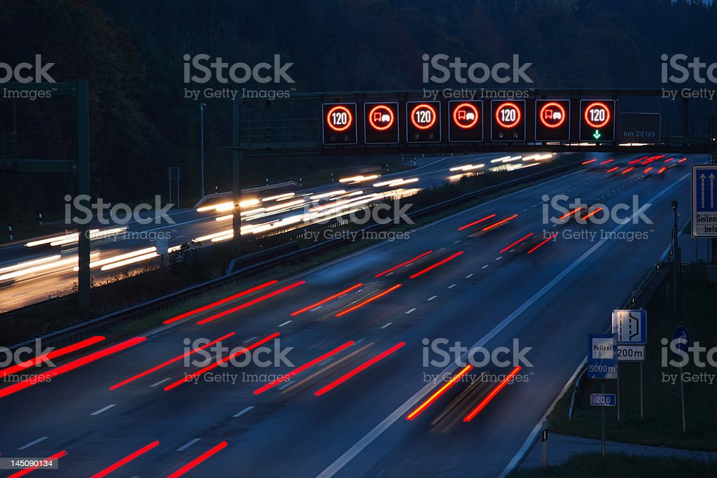 night traffic on german autobahn with illuminated speed limit signs royalty-free stock photo