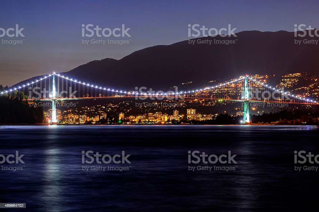 Night view of City, Bridge, Mountains, and Sea Water stock photo