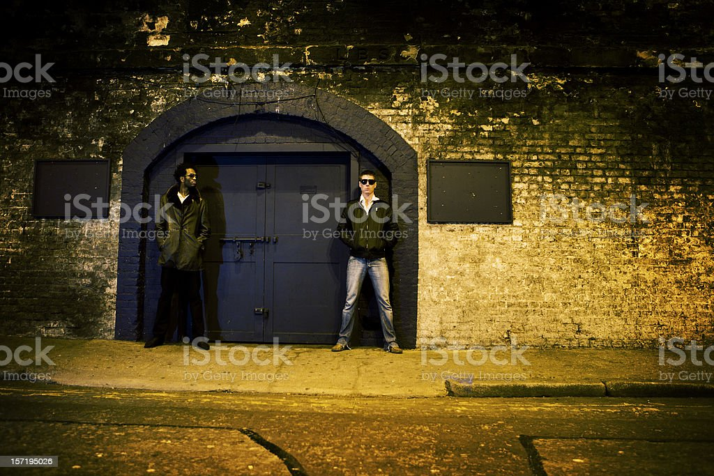 Nightclub bouncers standing outside an urban night club royalty-free stock photo