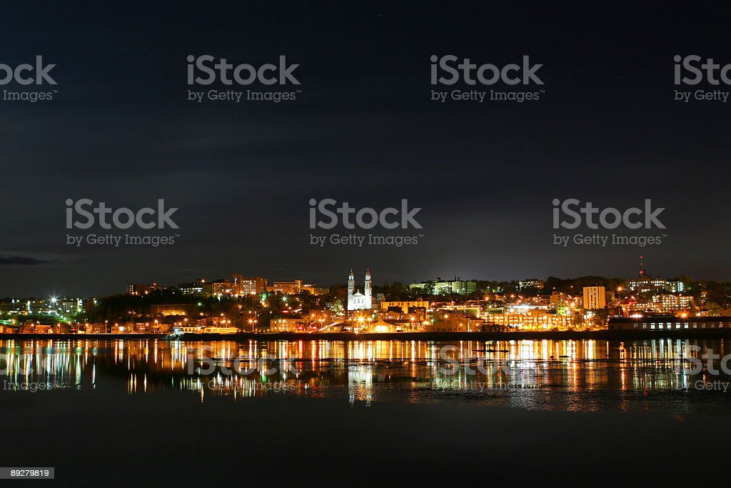 Nightime scene of Chicoutimi city reflection over the Saguenay river stock photo