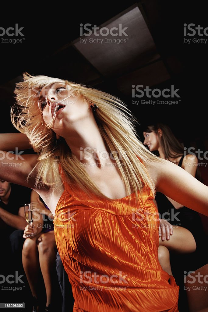 Nightlife - Young woman dancing with her friends in background royalty-free stock photo