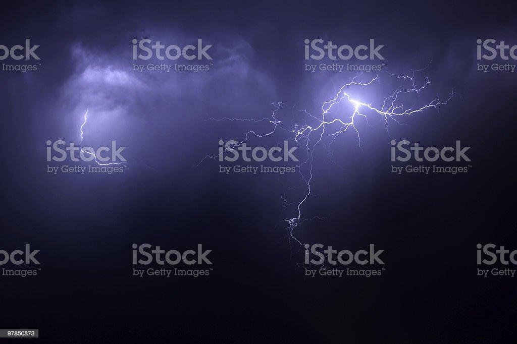 Nighttime lightening storm with streaks across purple sky royalty-free stock photo