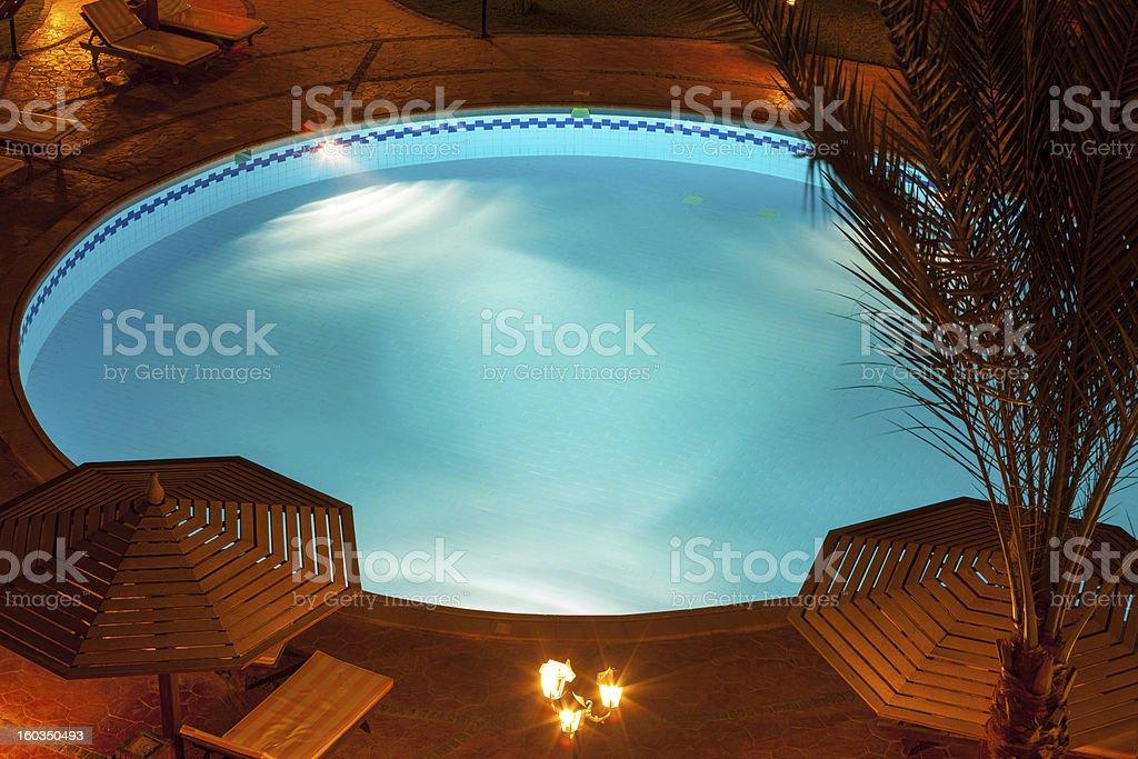 Nighttime setting of a luxury villa poolside royalty-free stock photo
