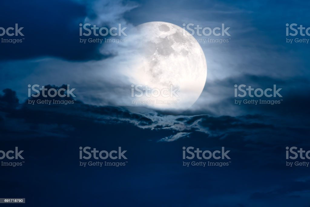 Nighttime sky with clouds and bright super moon with shiny. stock photo