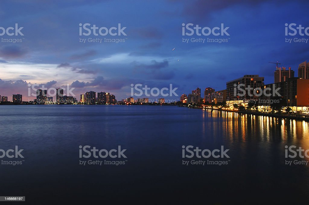 A nighttime view of a city by the water stock photo