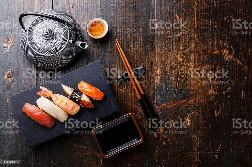 Nigiri sushi and tea on wooden background stock photo