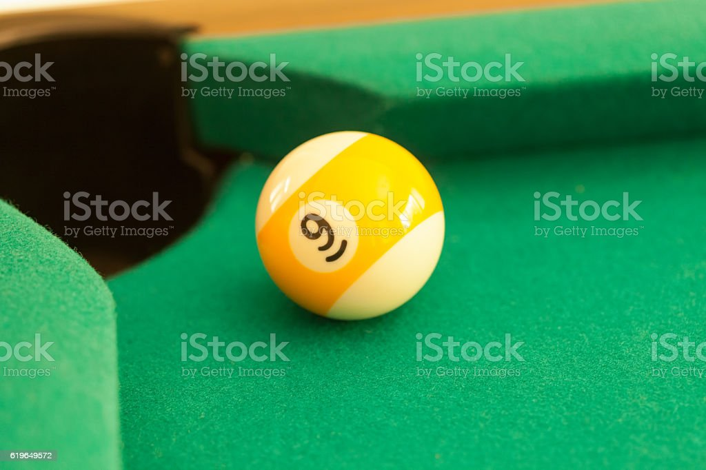Nine ball at the edge of the pocket stock photo