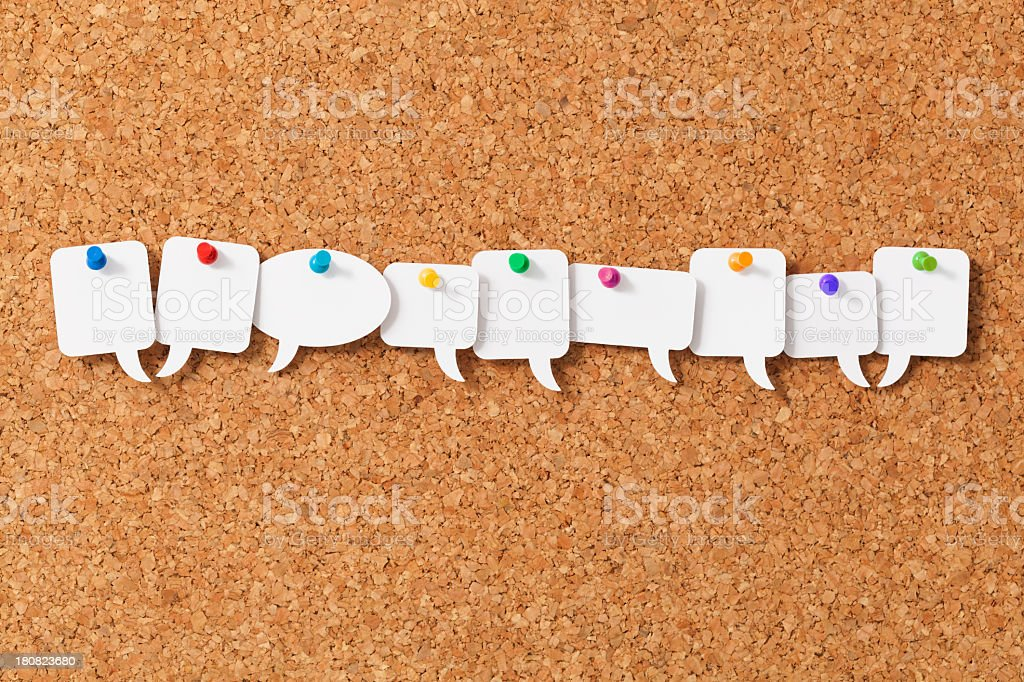 Nine blank white speech bubbles pinned to a notice board stock photo