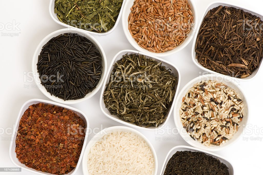 Nine small dishes with colorful tea leaves and rices stock photo