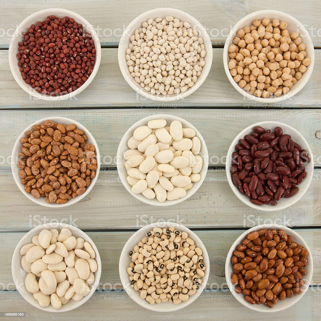 Nine varieties of Beans in white dishes on wooden table stock photo